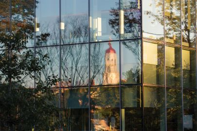 Harvard University tower reflected in the glass exteriror of Tata Hall