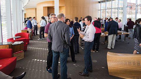 program participants socializing during break in the Tata Hall atrium at Harvard Business School