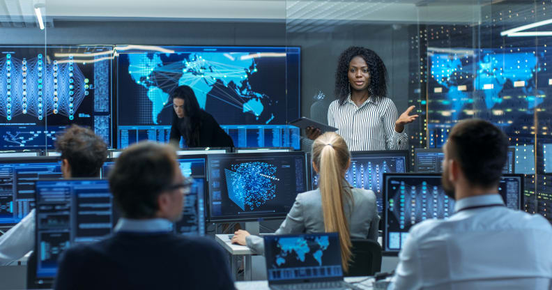 woman addressing four people all sitting in front of computer screens