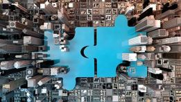 two large blue jigsaw puzzle pieces with bird's eye view of city below