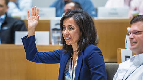 female participant with hand raised in executive education classroom