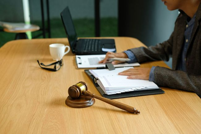 Hands on desk with papers and gavel