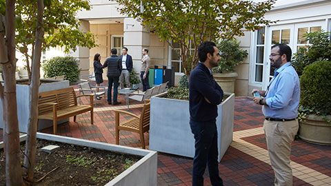 participants socializing in the McArthur Hall outdoor courtyard at Harvard Business School