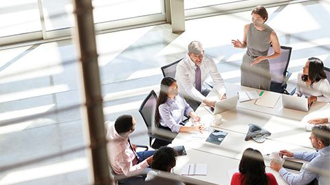 A woman executive talking to executives sitting around a conference table