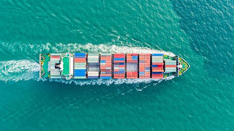 Bird's eye view looking at container ship on aqua water