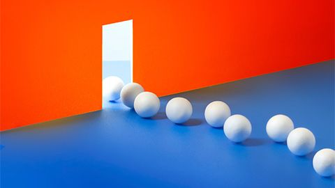 ping pong balls streaming across a blue floor and through a door in an orange wall