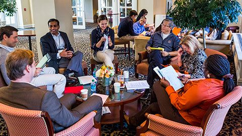 participants sitting around a small table during a study group session in the McArthur hall lounge