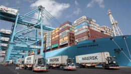 Maersk container ship at dock with 18-wheelers in foreground